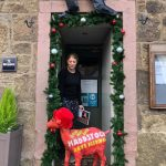 Red painted goat outside shop door, woman behind