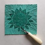 A sun shape has been cut into a lino tile to illustrate a linocut workshop.